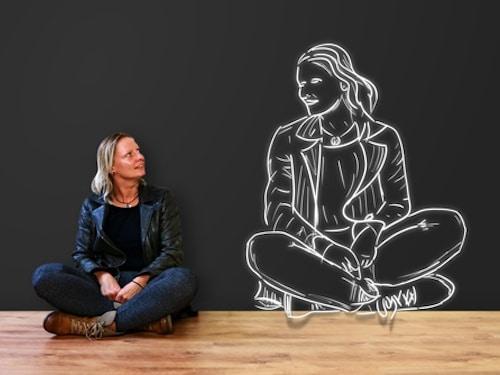 photo d'une jeune femme assise en tailleur qui regarde son image identique dessinée à la craie à ses côtés