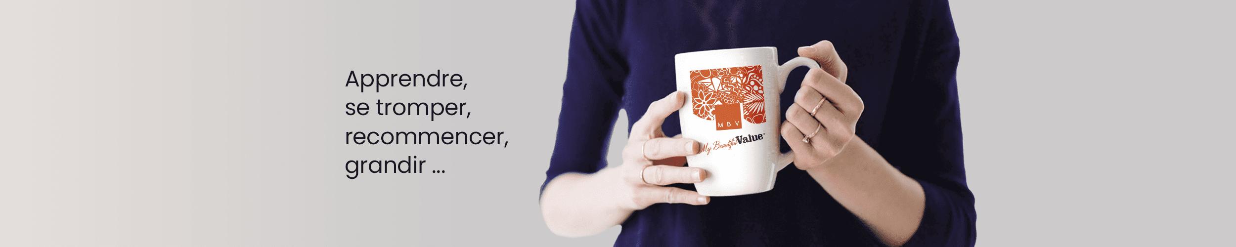 photo d'une jeune femme tenant une tasse sur laquelle se trouve le logo May Beautiful Value