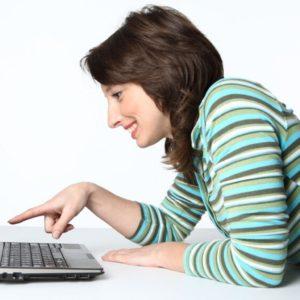 jeune femme devant un ordinateur portable en télétravail